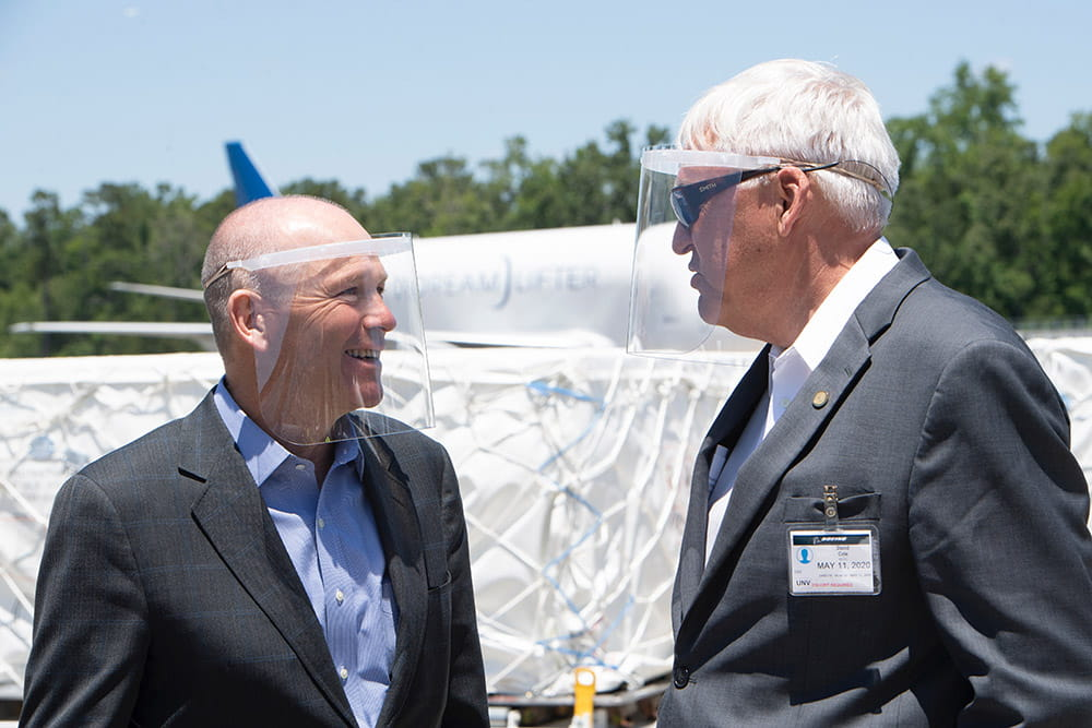 Boeing Global President and CEO Dave Calhoun and David J. Cole, M.D., FACS MUSC president speak to one another while wearing PPE.