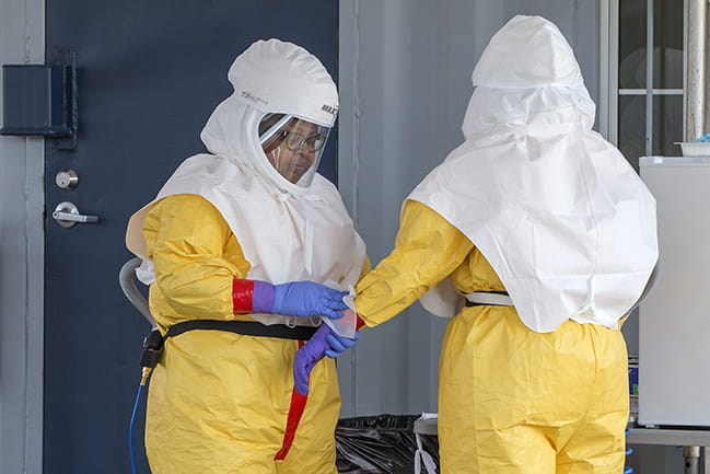Two healthcare workers wearing PPE at COVID-19 specimen collection site