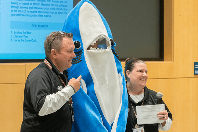 Photo of Shark Tank pitch contestants Bryan Wood and Kimberly Bailey posing with the MUSC shark.