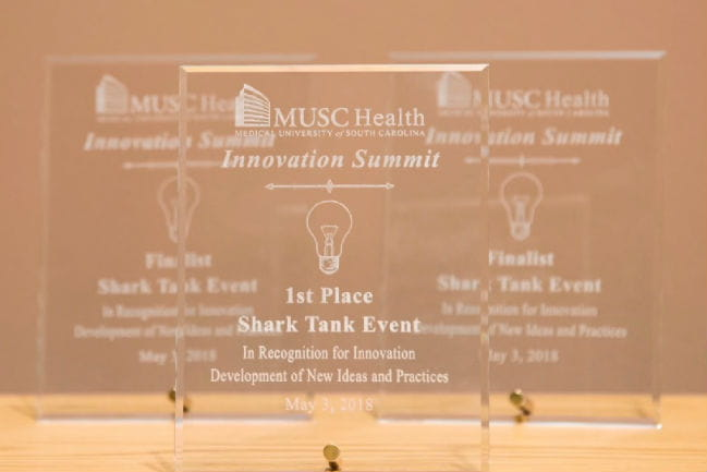 Image from Innovation Shark Tank video showing finalist and first place trophies.