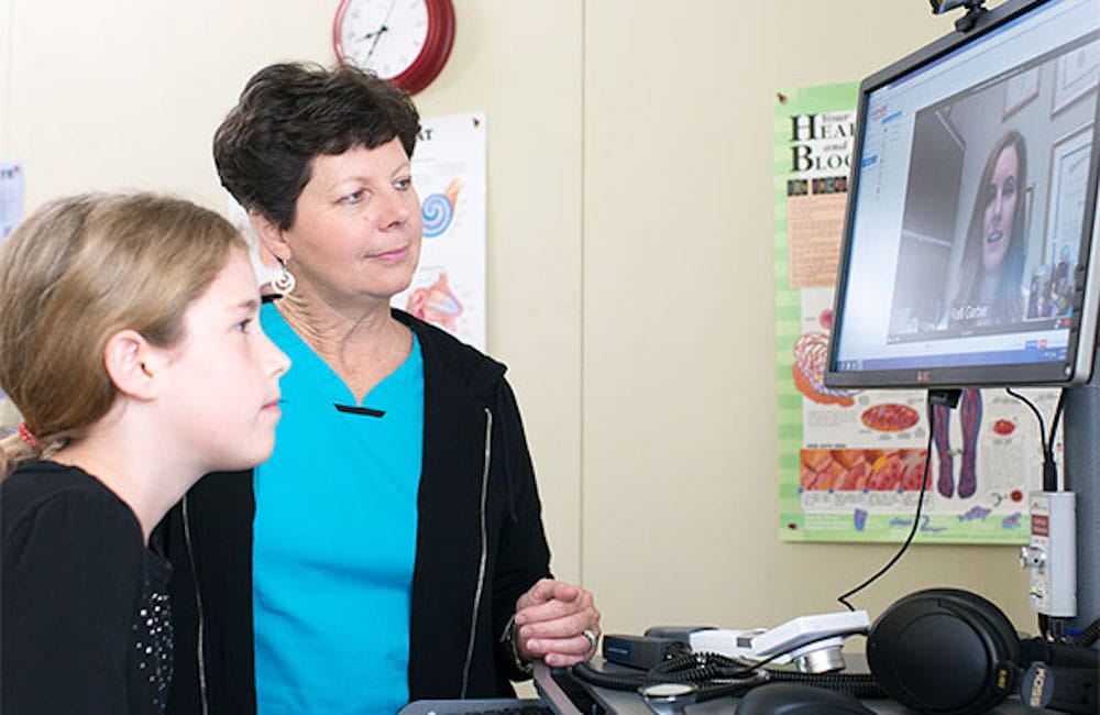 student Cadence Miles and nurse Lynn Floyd talk with nurse practitioner Kelli Garber, who's on the telehealth monitor