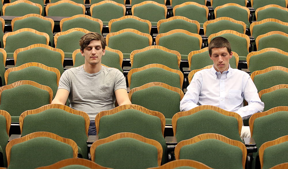 two students sit amid a theater-like auditorium of empty chairs with their eyes closed as they meditate
