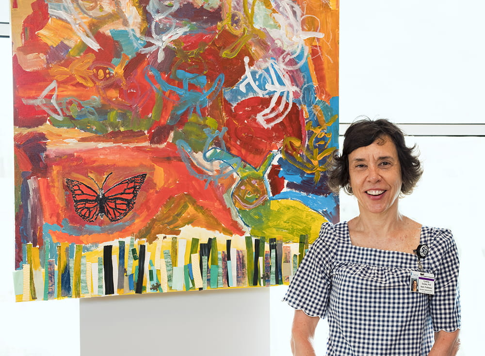 Cynthia Dodds stands in front of a large, vibrant red painting