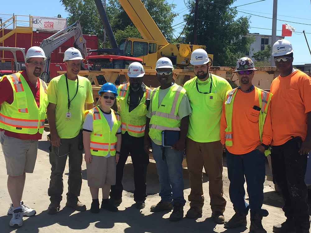 group photo of Riley Klim with workers