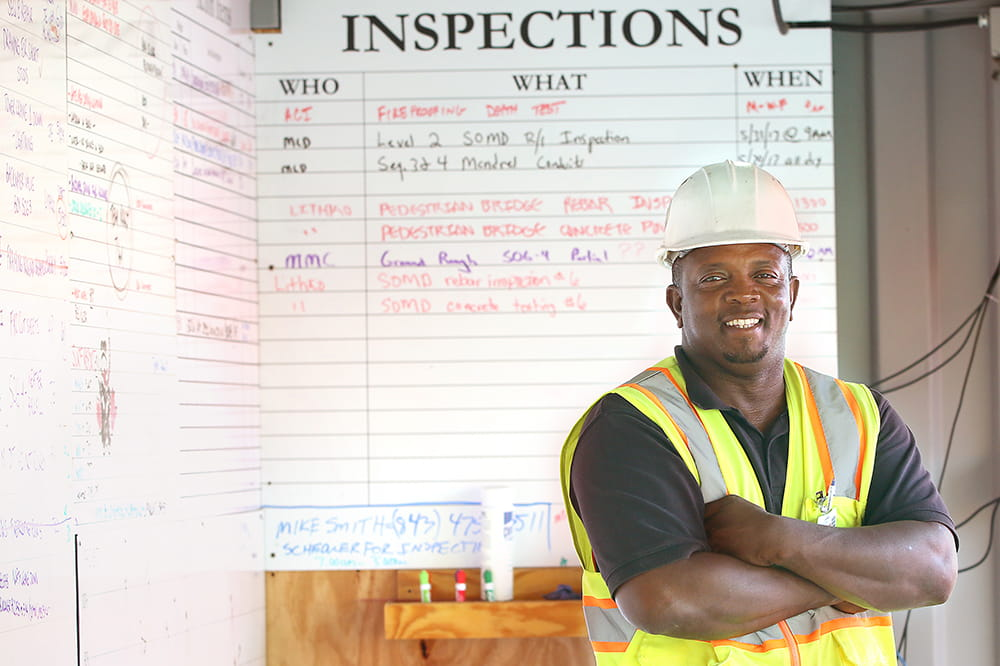 "Mike Smith poses in hard hat and safety vest in front of an ""inspections"" white board"