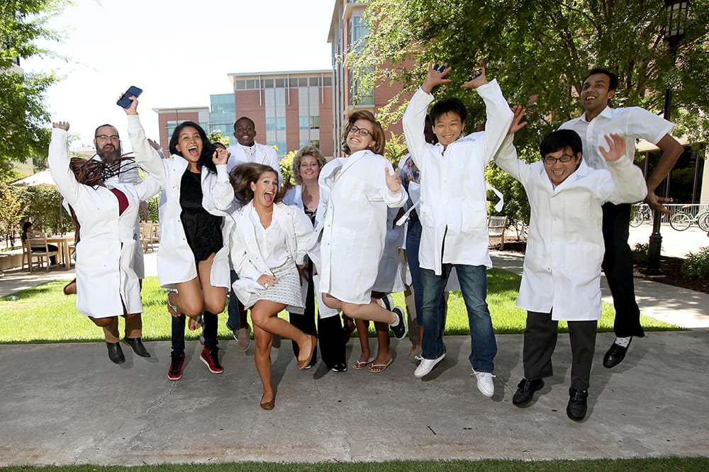Ann-Marie Broome is surrounded by interns in white lab coats leaping into the air