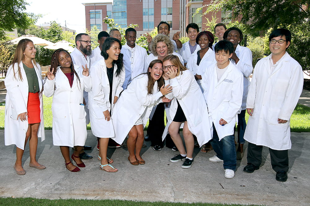 Ann-Marie Broome is surrounded by her summer interns in white lab coats