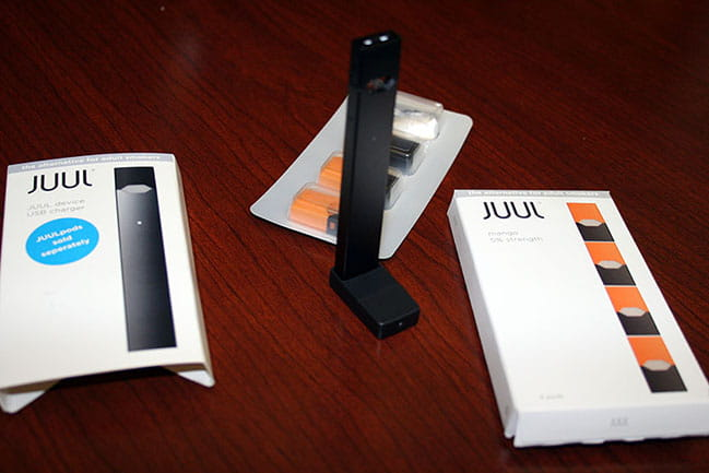 On the left, the package for a reusable Juul device that cost $38.99 at a Charleston vape shop. In the center, the Juul device itself, which looks like a flash drive, with nicotine-containing pods behind it. On the right, the package the $16.99 mango-flavored pods came in.