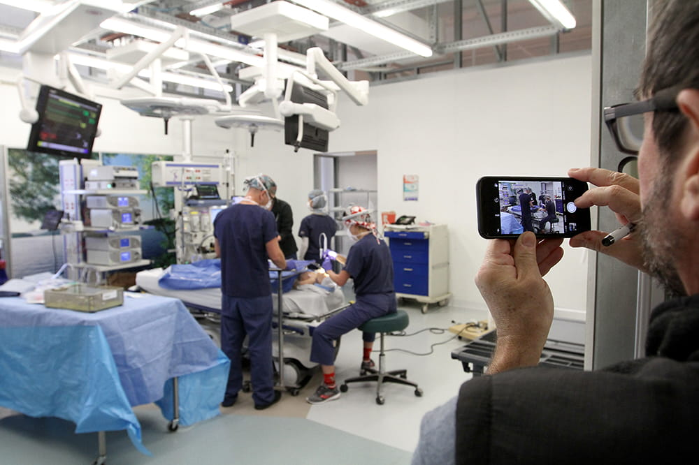 A man uses his phone to record a simulated surgery