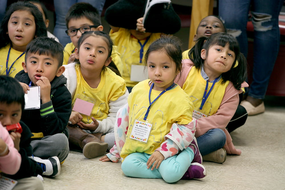 A group of kindergartners sit on the floor to listen to a presentation
