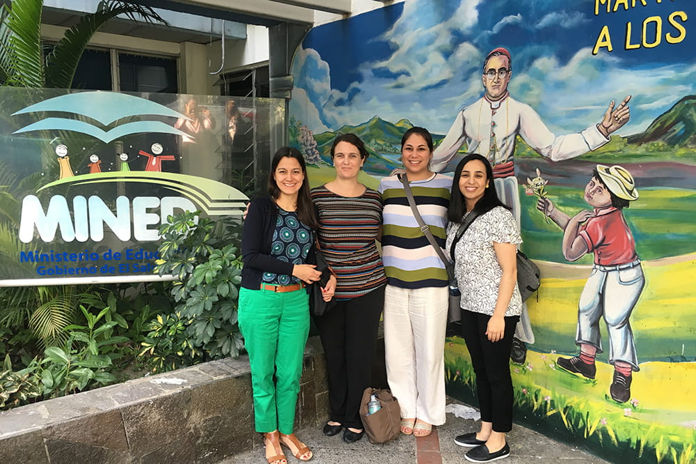 Four women pose in front of a colorful mural at the Ministry of Education in El Salvador