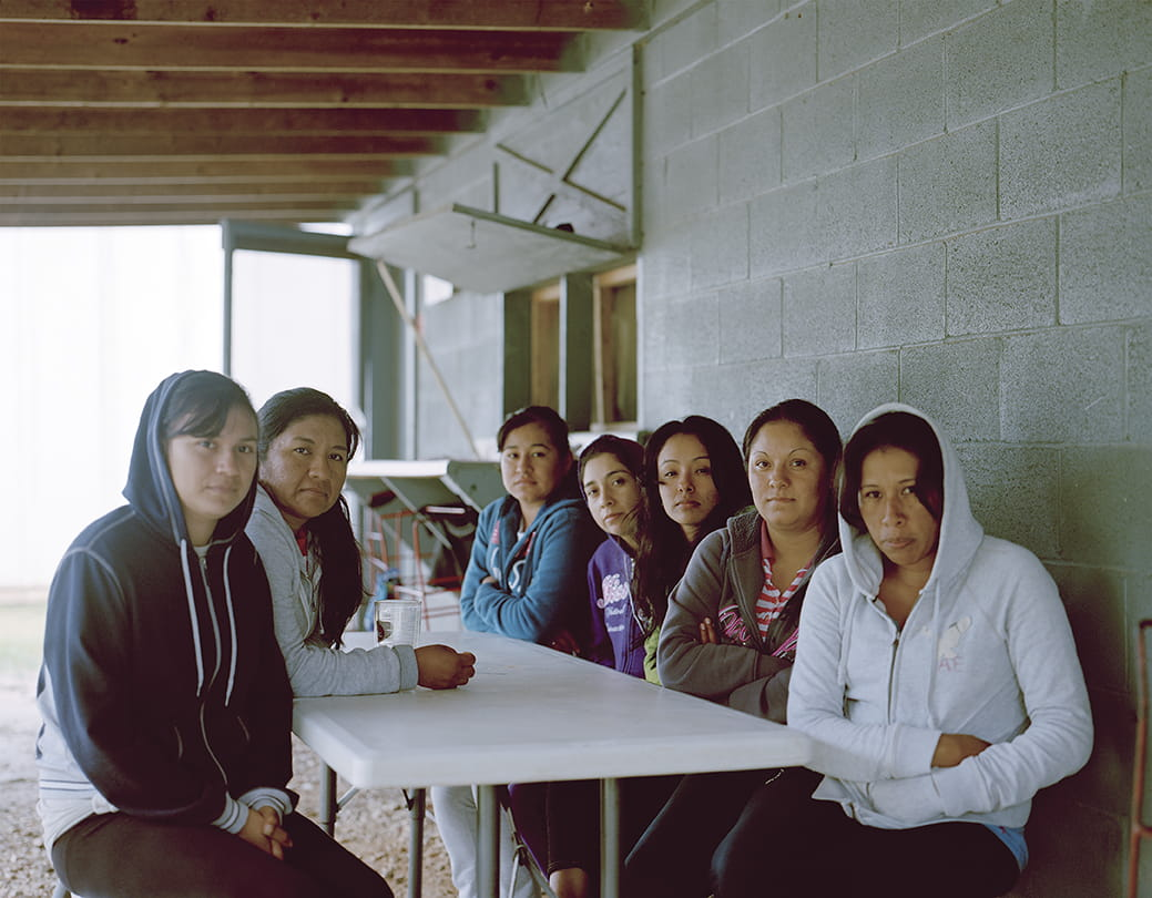 artistic photo of tired-looking migrant workers sitting at a table