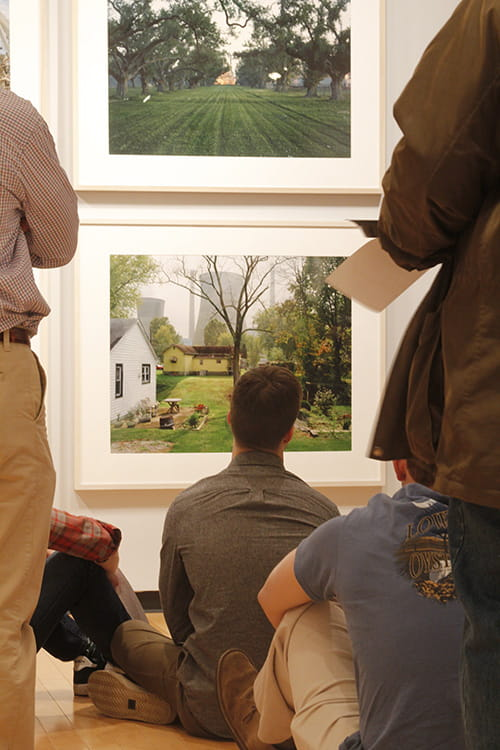 people sit on an art gallery floor looking at photographs