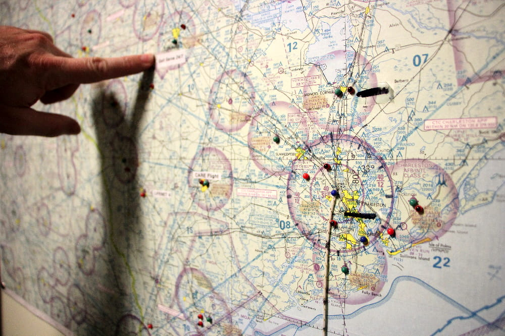 A pilot points to a location on a map inside the MEDUCARE flight control office.