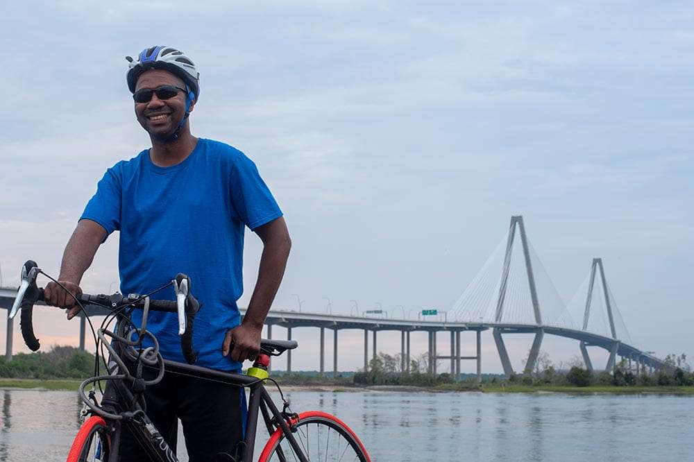 Man on a bike in front of the Arthur Ravenel Jr. Bridge