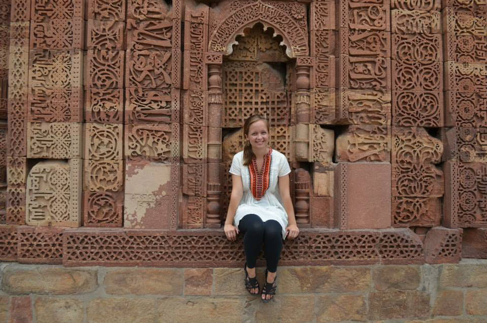 Shannon McGue sits by an elaborately carved tower in Delhi