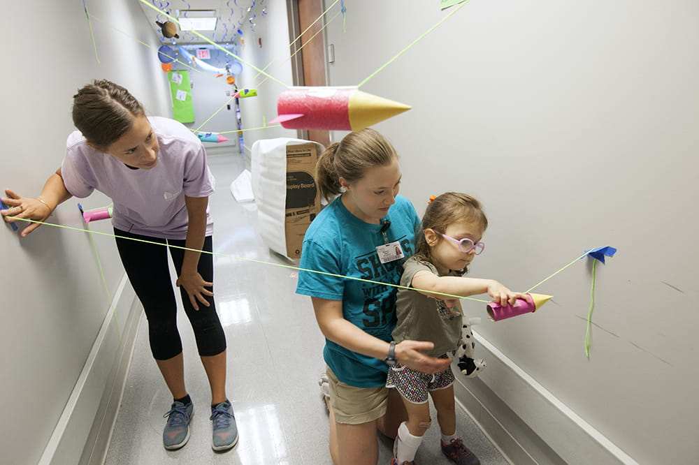 a little girl concentrates as she moves a cardboard tube along a string while a student helps her stand
