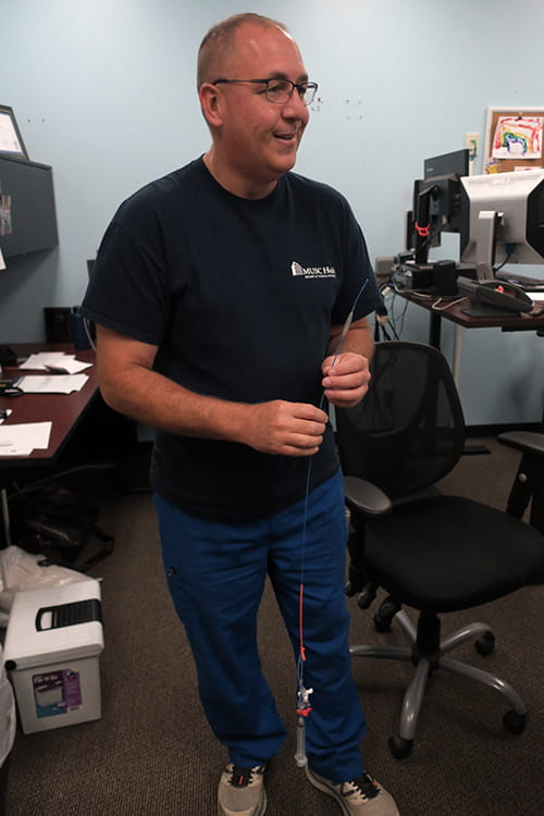 A man stands in an office and holds a long catheter tube called a REBOA