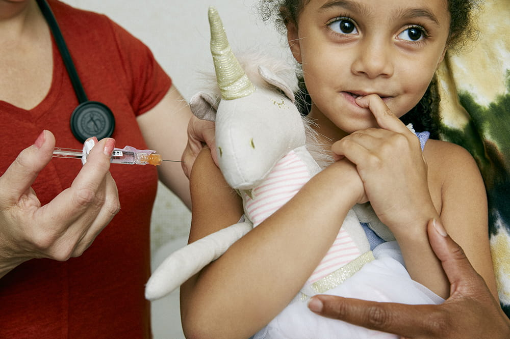 a girl clutches a stuffed unicorn as she's about to get a flu shot