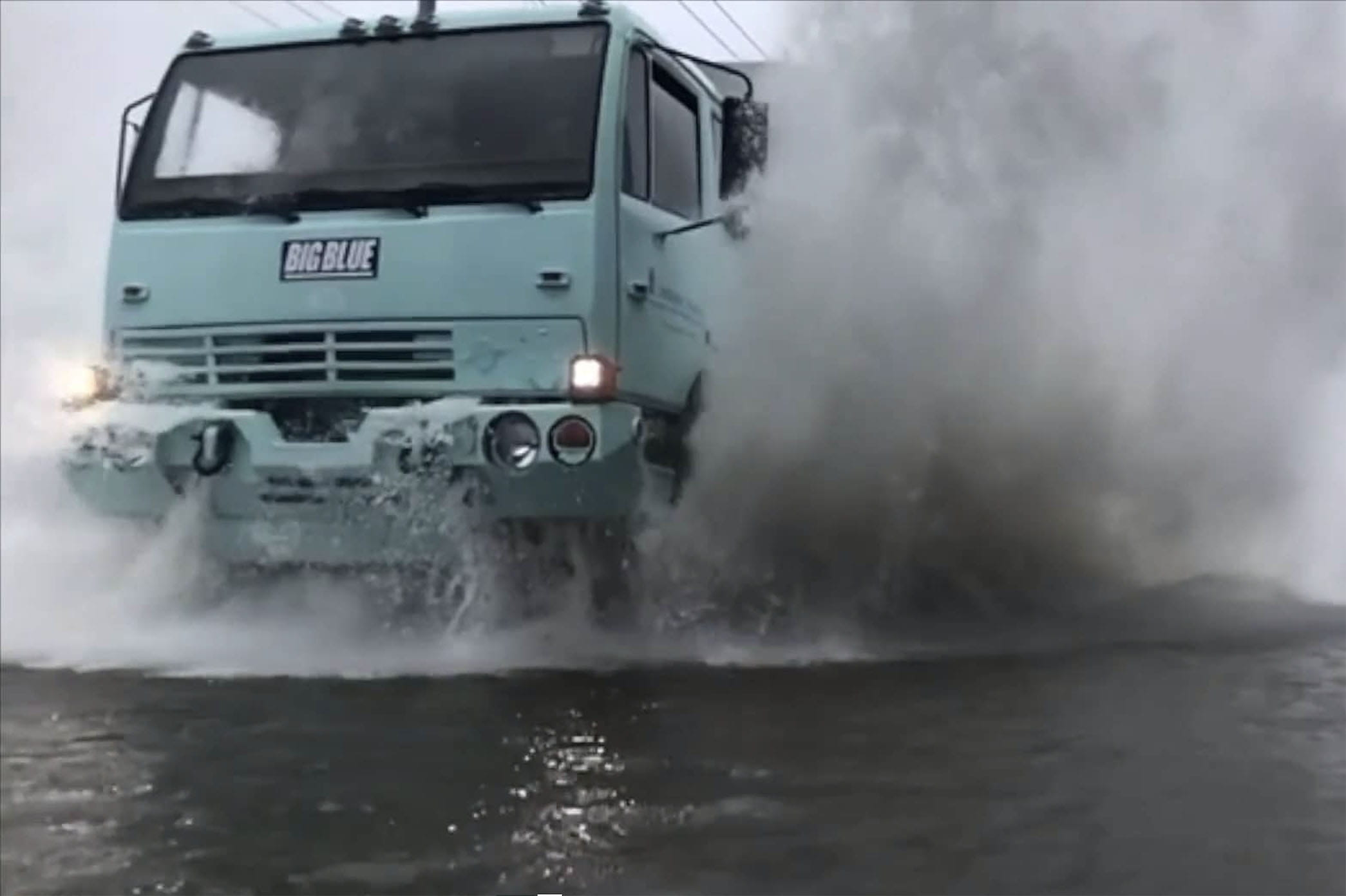 truck driving through flood waters
