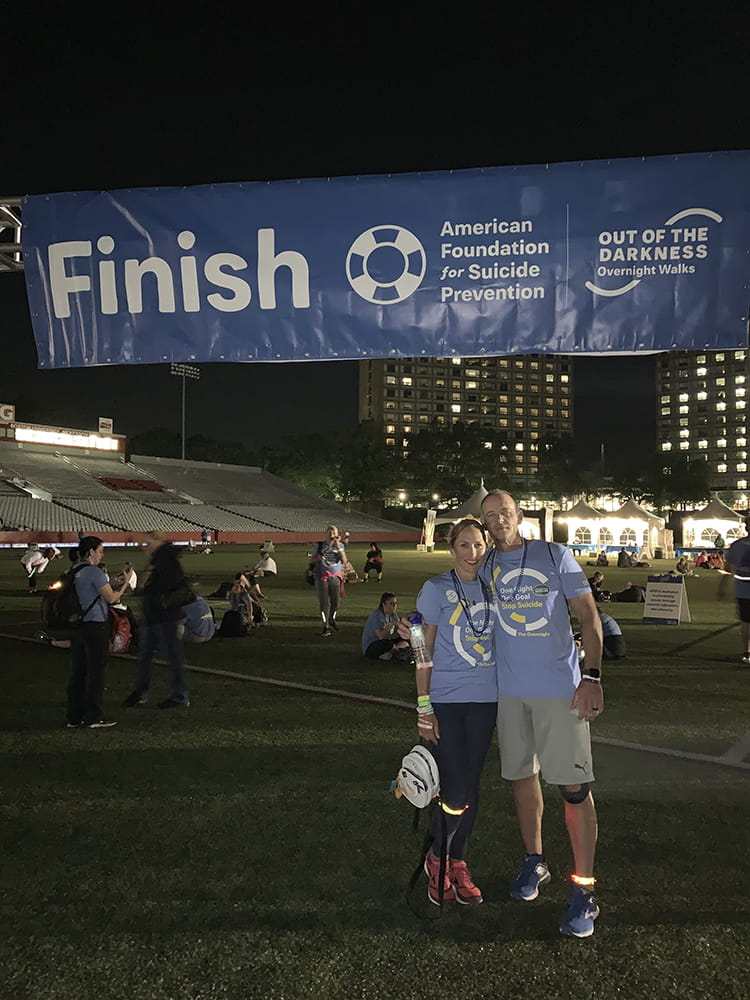 A man and woman at a large finish sign in the dark