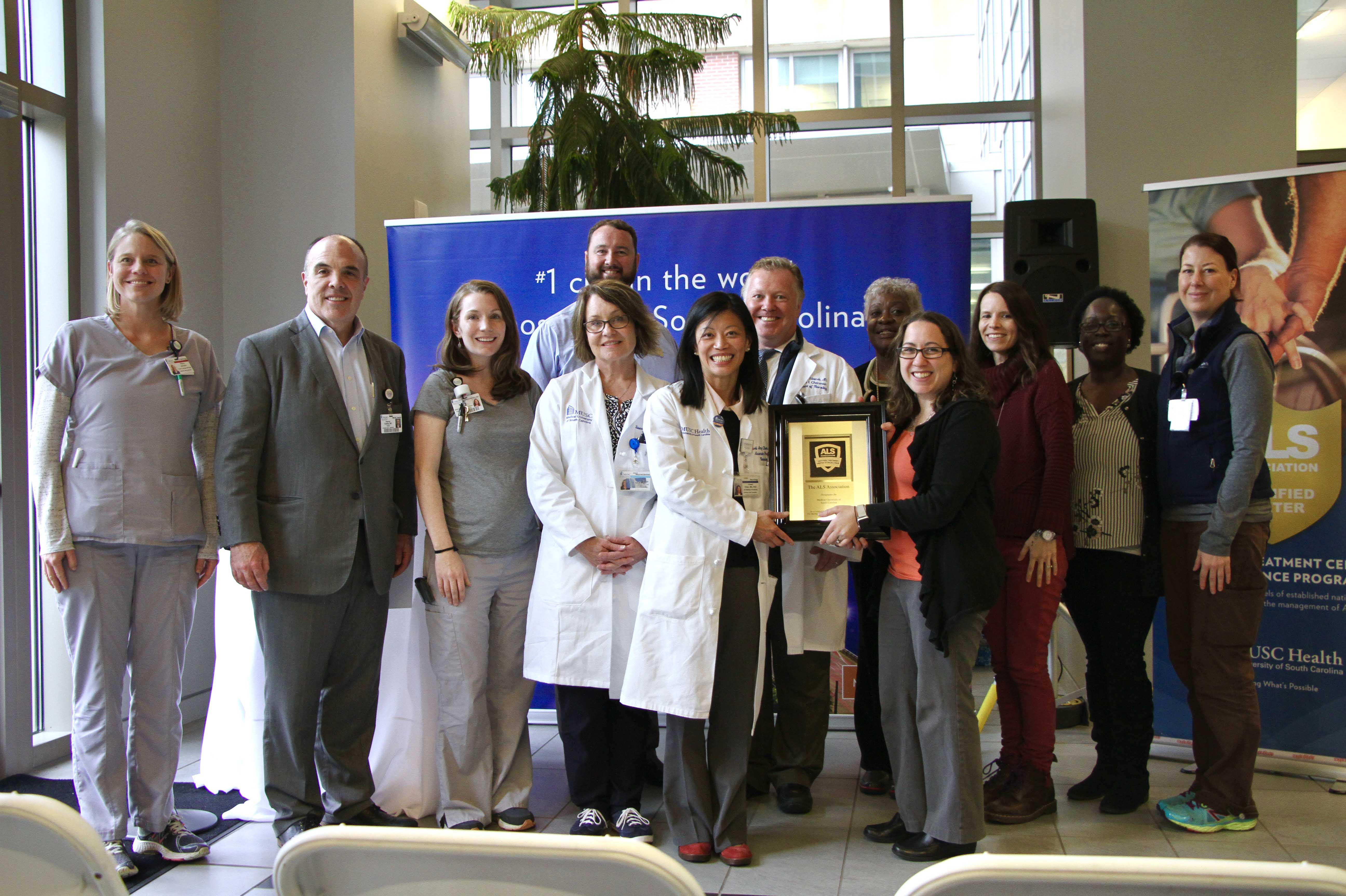 Members of MUSC's team as well as those from ALSA gather to pose for a photo holding a plaque commemorating MUSC being designated a Center of Excellence by the ALSA.