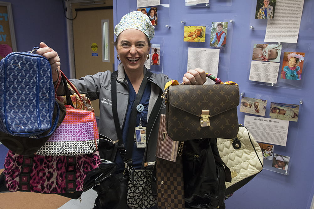 A woman in scrubs holds up dozens of purses on her arms