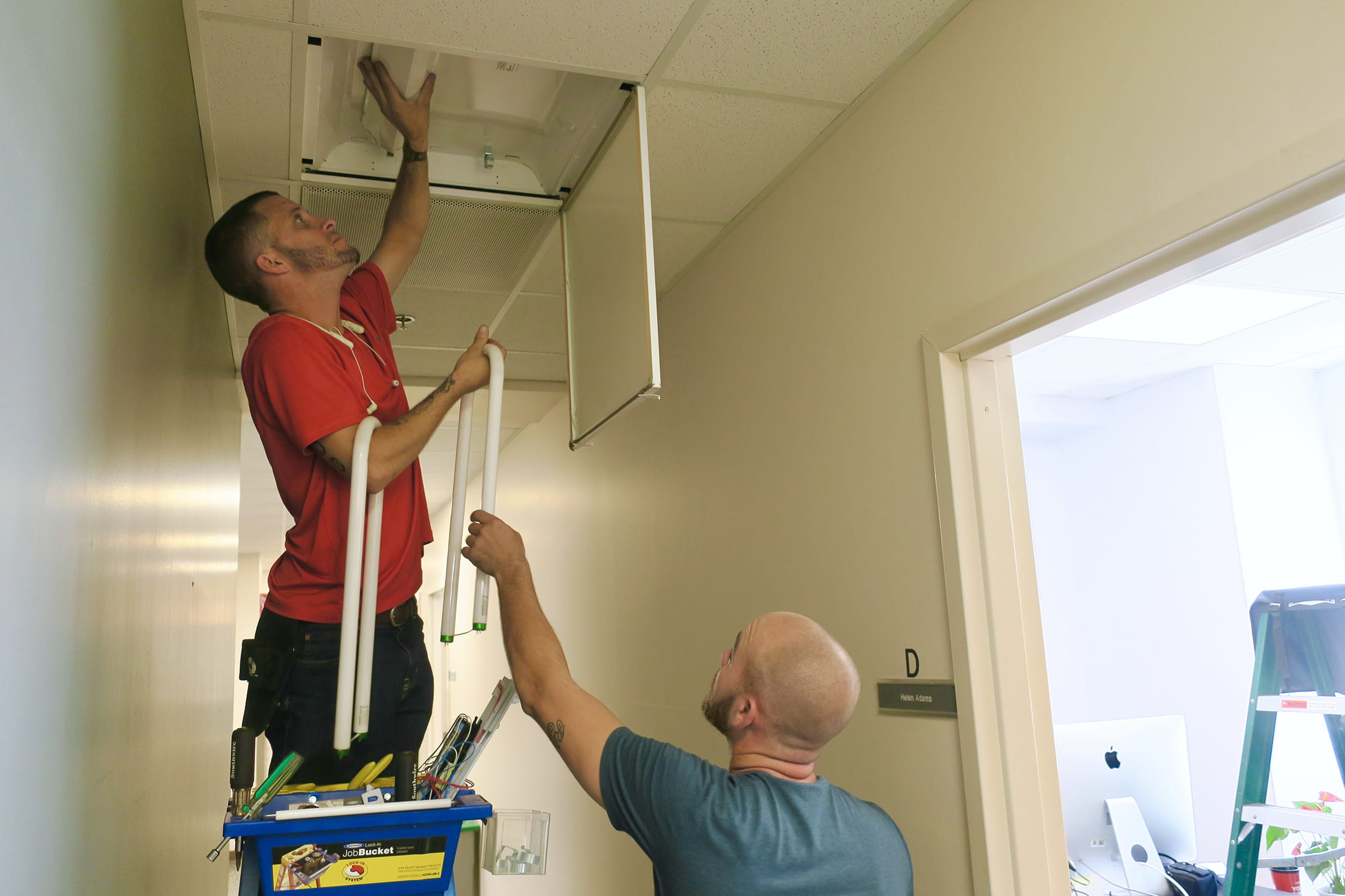 Electricians changing out fluorescent bulbs for LEDs inside MUSC's 135 Cannon Street facility