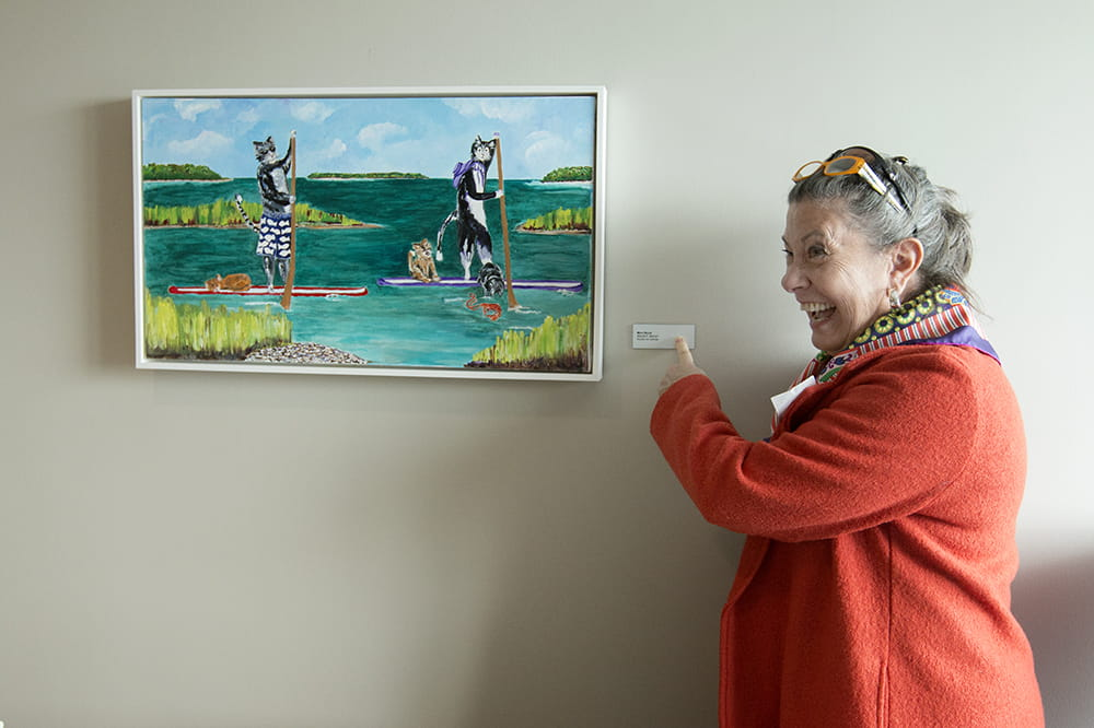 artist Mimi Wood points with glee at the nameplate by her artwork