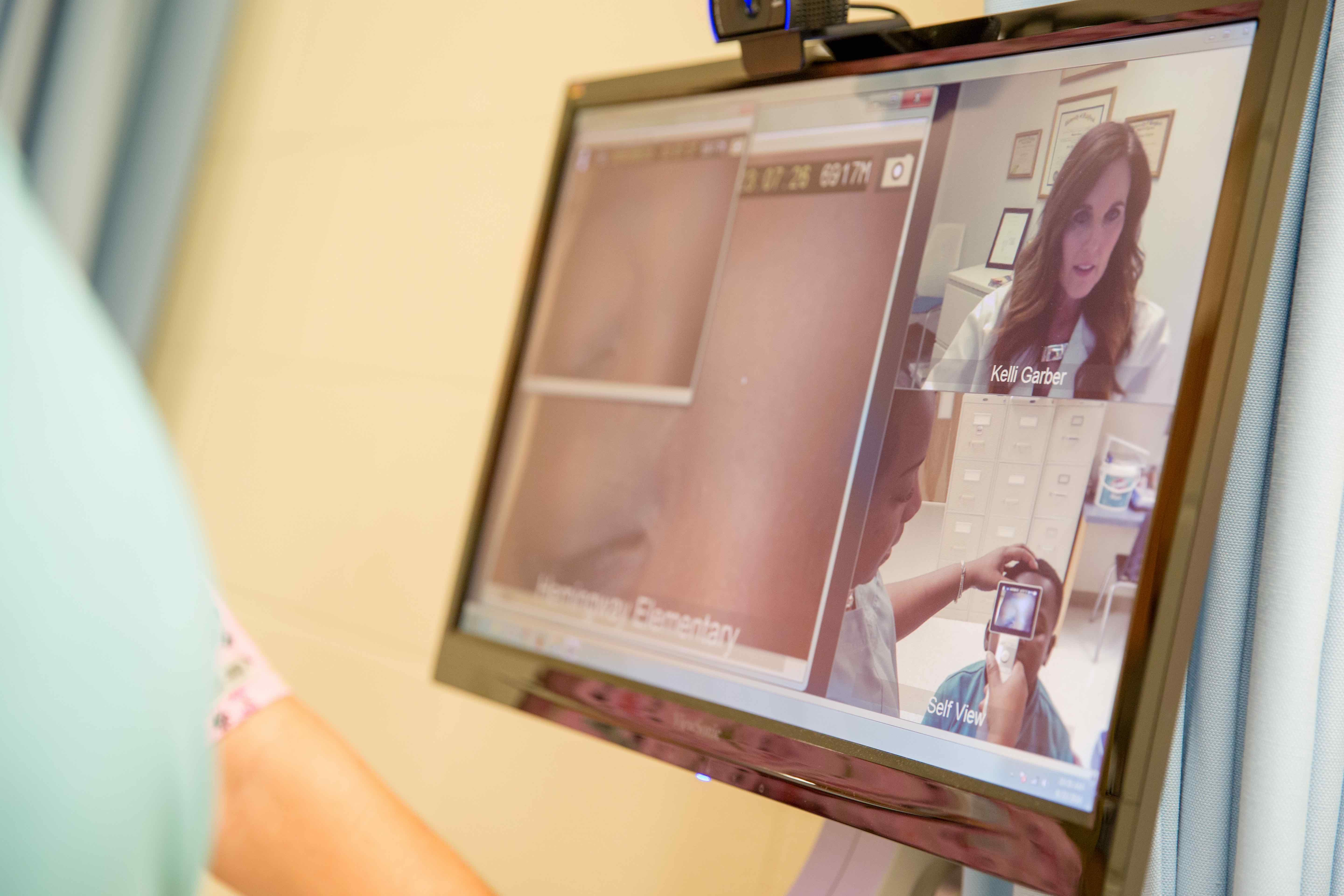 Close-up of Telehealth monitor showing Kelli Garber, MSN, APRN, lead nurse practitioner & clinical integration specialist at the Medical University of South Carolina Center for Telehealth, and a student