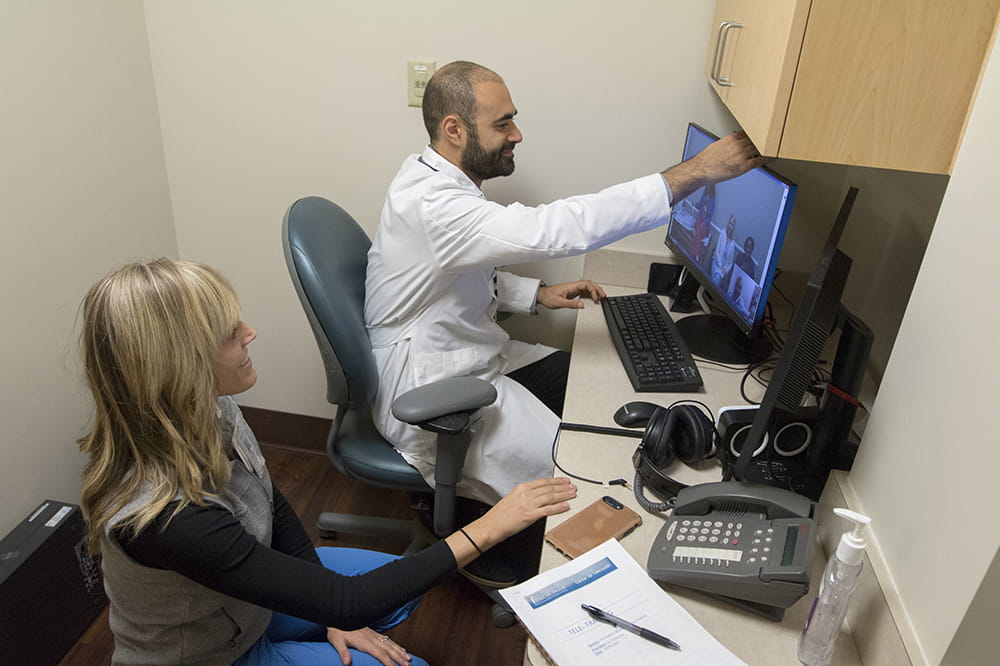 Dr. Soliman adjusts the camera on his computer screen in a small closet-like room as he prepares for telehealth visits.