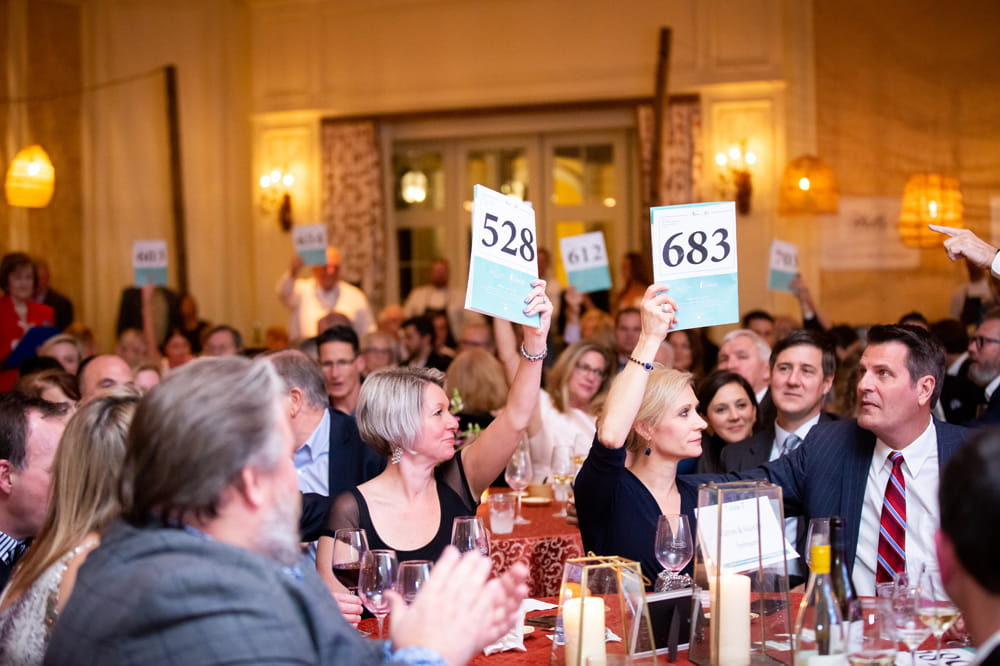 people at dinner table raise cards at an auction