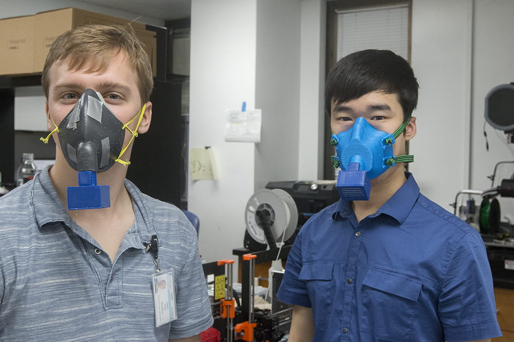 Two men pose with the 3D printed masks