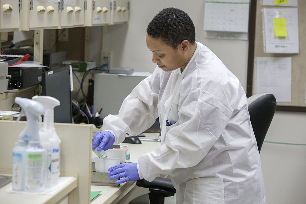 Medical lab technician Tanisha Dickerson puts saline solution into trays to prepare diagnostic instruments for testing.