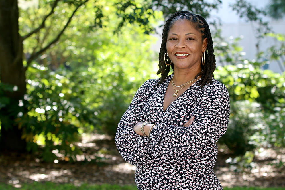 Chanita Hughes-Halbert stands outside under a tree