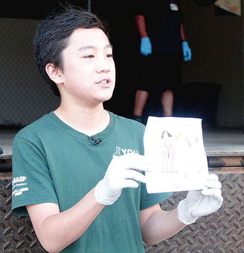 Buist Academy student Harry Ding shows off a hand-drawn picture from a child recognizing the need of supplies needed by the Lowcountry medical community in treating COVID-19.