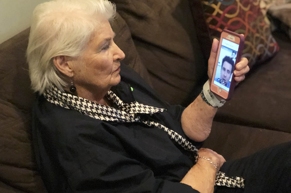 Sara Cutler uses her cell phone for a telehealth appointment
