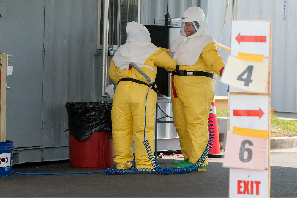 two women check each other's PPE. They are covered head to toe, wearing beekeeper-style hoods and baggy yellow jumpsuits