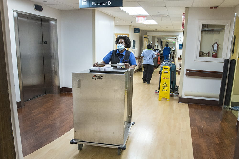 A woman pushes a large, enclosed stainless steel cart down a hospital hallway. The only other people in the hallway are other food service and environmental service employees.
