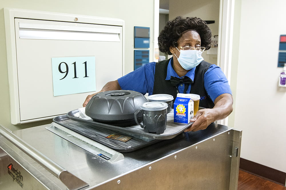 A woman takes a tray of food from a stainless steel cart to bring to a patient's room