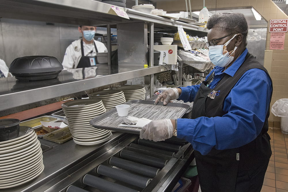 A woman in a commercial kitchen prepares a tray as the cook on the line behind her looks on
