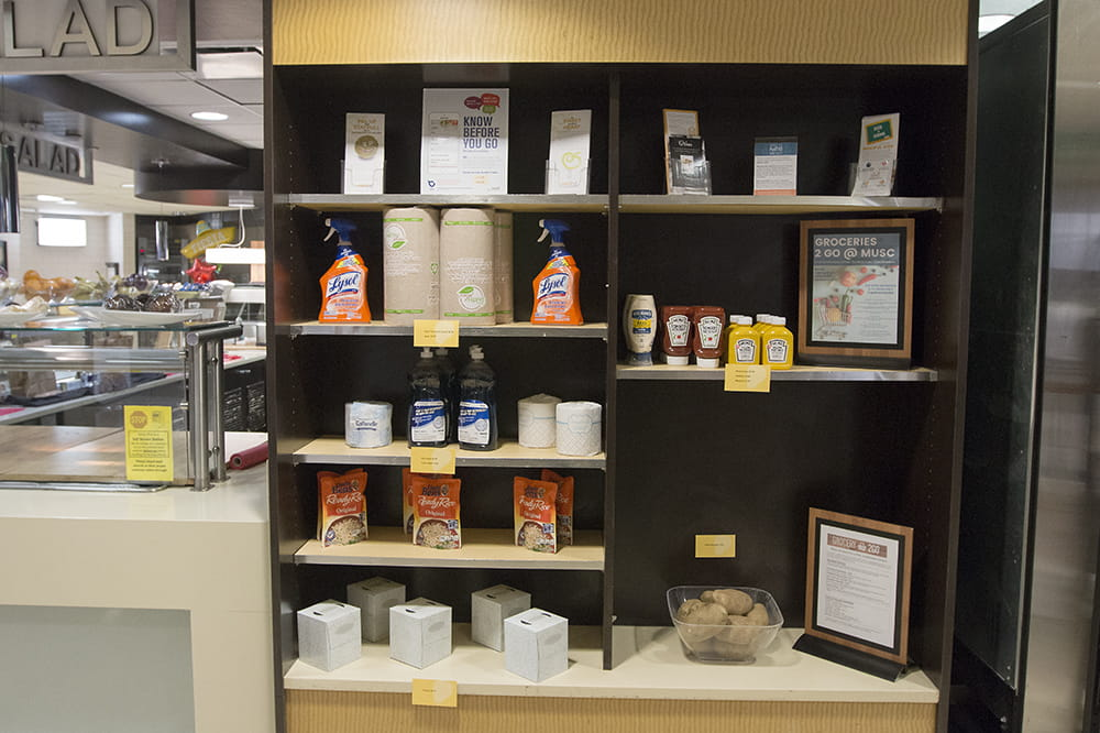 a photo of shelves in the cafeteria with various items like Lysol spray, toilet paper, ketchup, mustard and potatoes.