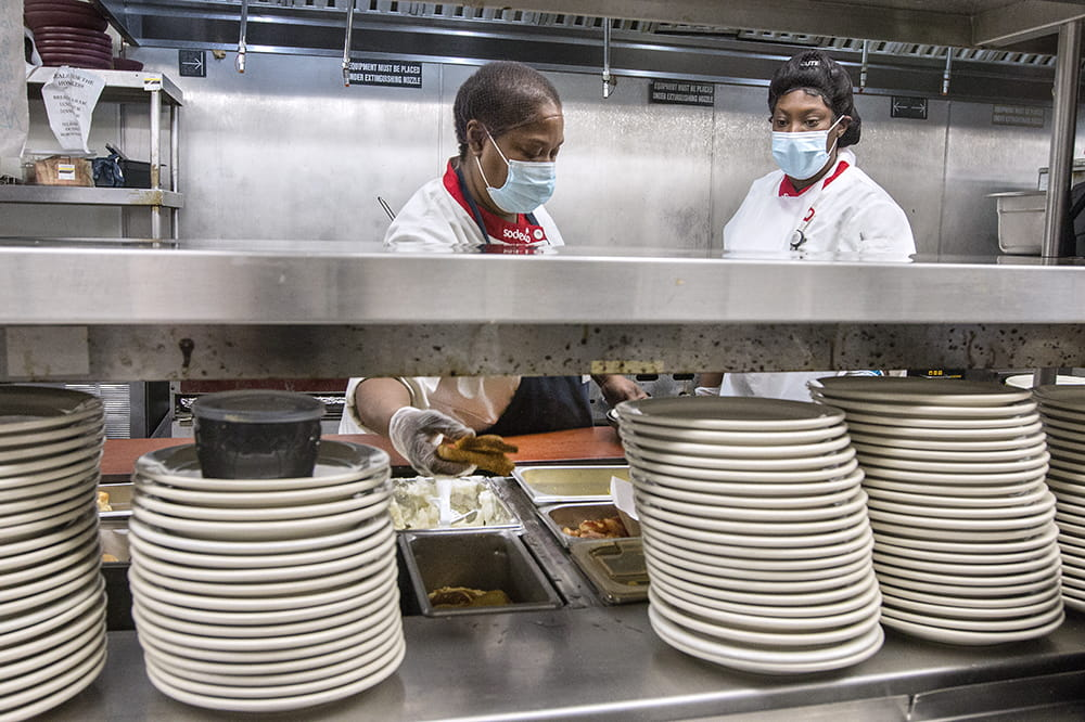 Two cooks are visible behind stacks of plates