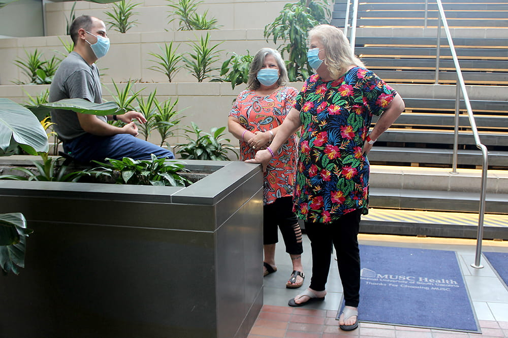 A man sits on the edge of an indoor planter chatting with two standing women