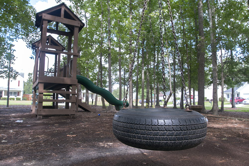 an empty tire swing hangs in front of a deserted play structure
