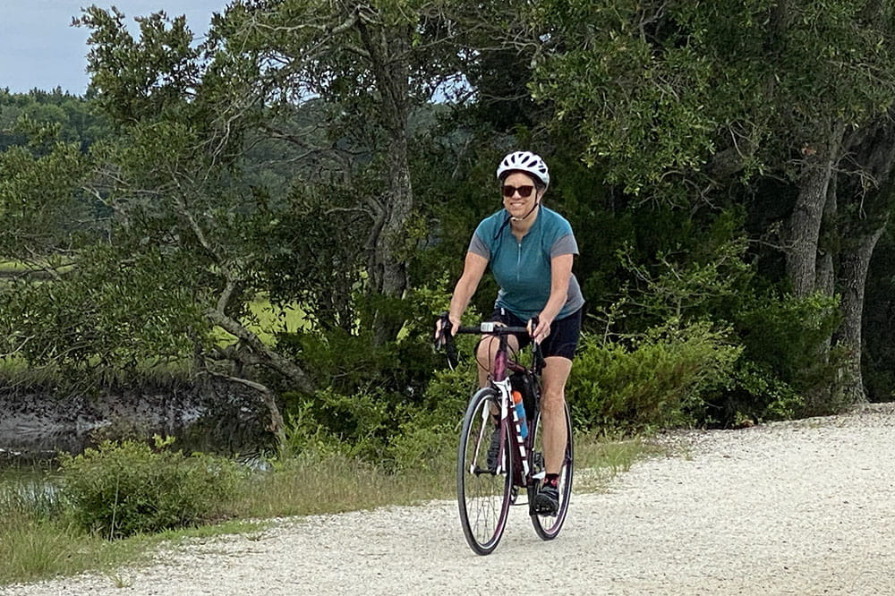 Kathy Hogan Edwards rides her bike on a nature trail