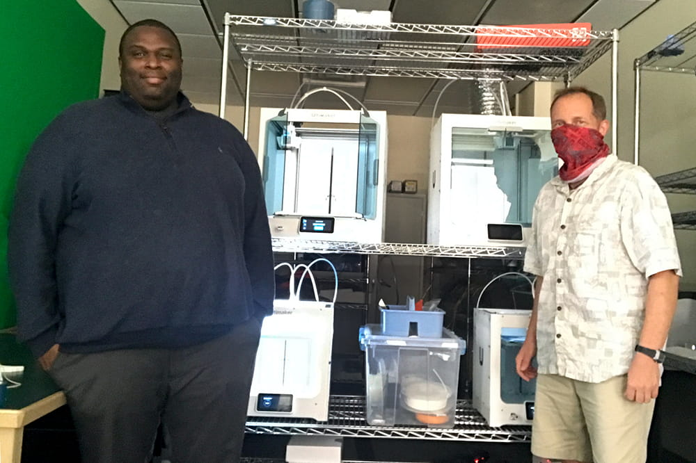 Lemon and Paggi pose in front of 3D printers