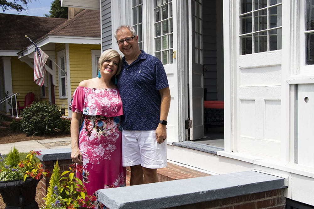 Jennifer and Mike Attisano stand on the steps in front of their house