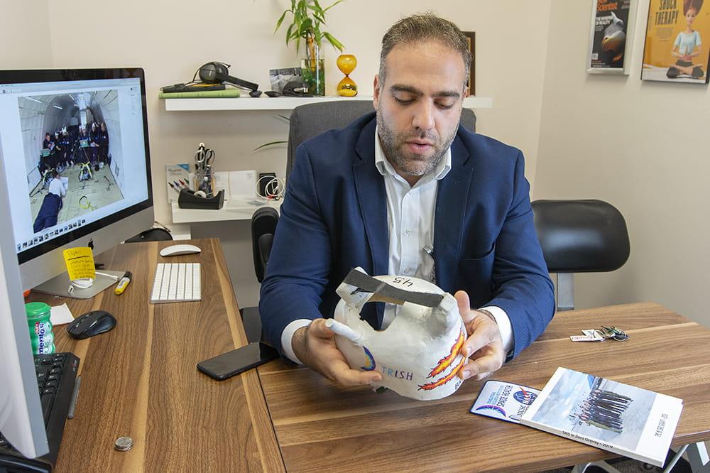 Badran sits behind a desk looking at a helmet he crafted