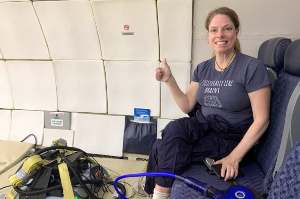 Dr Roberts, wearing a tee shirt that says I just really like brains, gives a thumbs up from inside the Zero Gravity plane